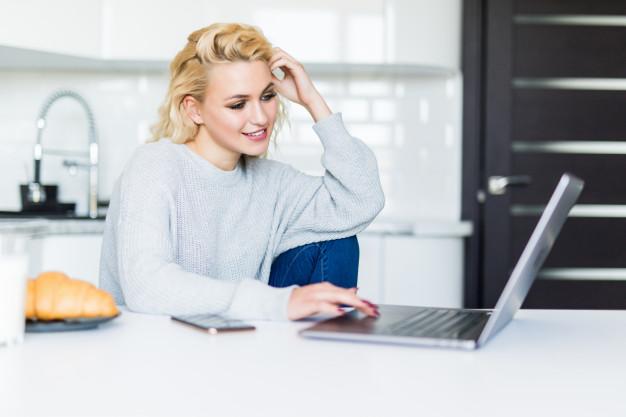 Home Office, roupas e produtividade. | https://br.freepik.com/fotos-gratis/mulher-loira-sorridente-tomando-cafe-da-manha-e-usando-seu-laptop-na-cozinha_8472824.htm#page=4&query=home+office&position=15
